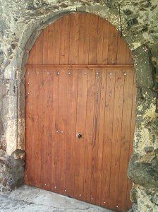 Porte de garage en arc de cercle, entourée d'une maçonnerie de pierres.