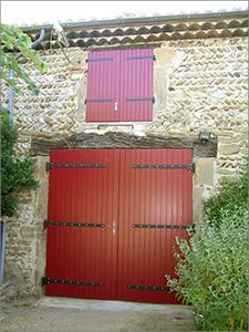 Vue de volets de fenêtre et d'un garage. Peint ocre rouge.